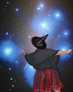 Woman in a witches hat and clothing pointing to a star with her wand