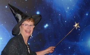 Women in witches hat and with want pointing to stars