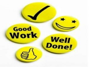 "Bright yellow round badges with messages like ""Good Work"", smiley faces and thumbs up"