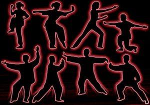 Women and men as silhouettes doing tai chi.