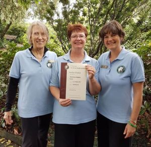 Three smiling women, one in the middle holding a certifcate