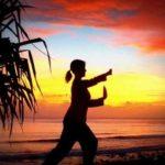 Woman doing tai chi on a beach at sunset