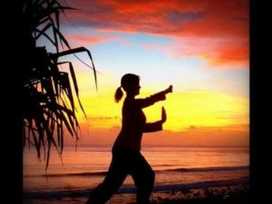 Woman doing tai chi on a beach at sunset