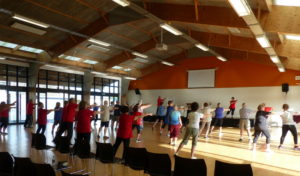 Photo of a group of people doing tai chi in a big sunny hall.