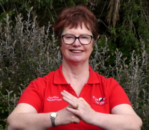 A smiling woman in a red shirt, with her hands positioned in the tai chi welcome greeting
