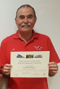 Smiling man in red shirt holding a certificate