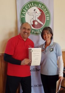 Man in red shirt smiling as he is awarded his certificate by a woman in a blue shirt