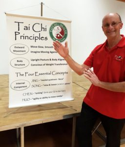 Man in red shirt doing a tai chi pose next to a big chart