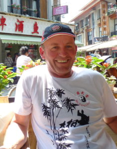 Smiling man in white t-shirt with Chinese design on it, sitting at a cafe in a Chinese town