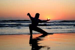 Person doing tai chi on the beach at sunset. One hand appears to capture the sun just as it is setting.