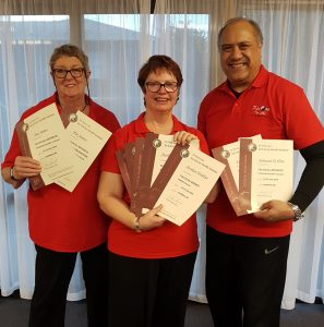 Three smiling people in red shirts, each holding several certificates.
