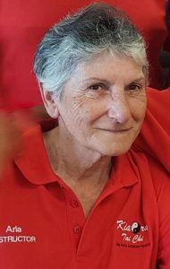 Head and shoulder photo of a smiling woman wearing a red shirt