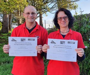 Smiling man and woman, both in red shirts and holding achievement certificates