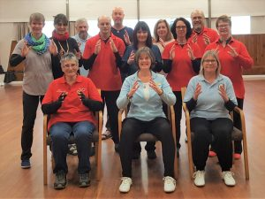 "Group photo of smiling people showing the hand movement for ""open and close"" in Tai Chi for Arthritis"